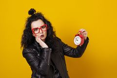 Beautiful surprised young woman with alarm clock standing in fro. Nt of a yellow background stock images