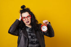 Beautiful surprised young woman with alarm clock standing in front of yellow background. Stock Images