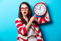 Beautiful surprised young woman with clock standing in front of Royalty Free Stock Images