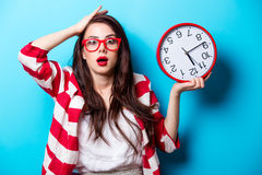 Beautiful surprised young woman with clock standing in front of Stock Image