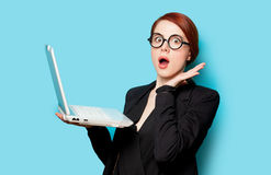 Beautiful surprised young woman with laptop on the wonderful blu Stock Images