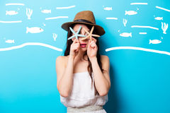 Beautiful surprised young woman with starfishes standing in fron Stock Photos