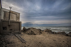 Beautiful surreal landscape of abandoned house and ladder on rocky seashore at sunset time. Cloudy weather. Caspian Sea, Azerbaija. N, Novkhani royalty free stock photo