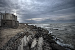 Beautiful surreal landscape of abandoned house and ladder on rocky seashore at sunset time. Cloudy weather. Caspian Sea, Azerbaija Stock Photography