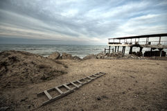 Beautiful surreal landscape of abandoned house and ladder on rocky seashore at sunset time. Cloudy weather. Caspian Sea, Azerbaija Royalty Free Stock Image