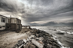 Beautiful surreal landscape of abandoned house and ladder on rocky seashore at sunset time. Cloudy weather. Caspian Sea, Azerbaija Royalty Free Stock Images