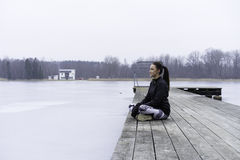 Beautiful Swedish caucasian fitness teen girl sitting on wood bridge outdoor in winter landscape Stock Photos