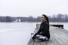 Beautiful Swedish caucasian fitness teen girl sitting on wood bridge outdoor in winter landscape Stock Image