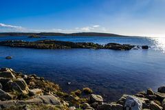 Beautiful Swedish coastal nature and landscape with shimmering water and a rocky shore. stock photos