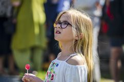 Beautiful swedish happy kid with candy is enjoying traditional decoration of mid summer day with colourful dresses stock photos