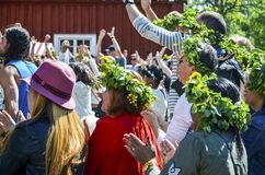 Beautiful swedish kid wearing colourful leave crown with mom is enjoying traditional decoration of mid summer day. Umea, Sweden - JUNE 23, 2017, mid summer day stock images