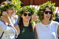 Beautiful swedish sweet happy womans are enjoying traditional decoration of mid summer day wearing colourful leave crown in sunny. Umea, Sweden - JUNE 23, 2017 stock photo