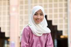Beautiful and sweet Asian Malay Muslim lady. Photo of a beautiful asian malay muslim lady in traditional baju melayu costume, in front a mosque in Malaysia Royalty Free Stock Image
