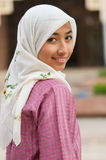 Beautiful and sweet Asian Malay Muslim lady. Photo of a beautiful asian malay muslim lady in traditional baju melayu costume, in front a mosque in Malaysia Stock Photo