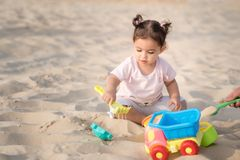 Beautiful sweet Baby girl playing on the sandy summer beach near the sea. Travel and vacation with children. stock image