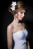 Beautiful sweet gentle girl groom in a wedding dress with a wreath and flowers in her hair in the studio Royalty Free Stock Image