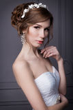 Beautiful sweet gentle girl groom in a wedding dress with a wreath and flowers in her hair in the studio Stock Images