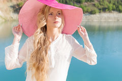 Beautiful sweet gentle girl in white dress in light big pink hat on the shore of the blue sea at sunset summer evening sun Stock Photos