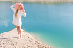 Beautiful sweet gentle girl in white dress in light big pink hat on the shore of the blue sea at sunset summer evening sun Royalty Free Stock Image