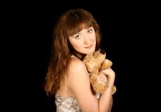 Beautiful sweet girl with a bear in the hands. On black background Stock Image
