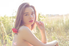 Beautiful sweet girl with big lips plump with poppy in hand walking in a field on a sunny day at sunset with bared shoulders. Beautiful sweet girl with big lips Stock Images