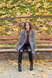 Beautiful sweet girl with the big sad eyes in coat sitting on the bench in the fall among the fallen yellow leaves autumn bright royalty free stock photography