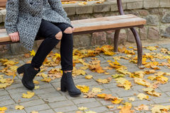 Beautiful sweet girl with the big sad eyes in coat sitting on the bench in the fall among the fallen yellow leaves autumn bright. Beautiful sweet girl with the Stock Photo