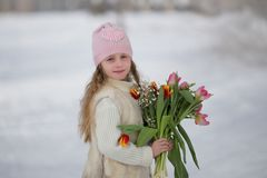 Beautiful sweet girl with a bouquet of tulips in the park in spring stock photo
