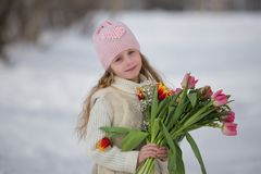 Beautiful sweet girl with a bouquet of tulips in the park in spring royalty free stock photos