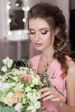 Beautiful sweet girl bridesmaid preparing for the wedding of a friend in the pink evening dress with evening hairstyle and bright stock photography