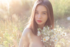 Beautiful sweet girl with full lips sitting in a field with a bouquet of daisies with obnozhennymi shoulders at sunset in the sunl Royalty Free Stock Image