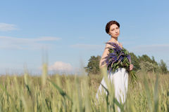 Beautiful sweet girl with a plait hair in a white summer sundress walking in a field with a bouquet of purple lupine flowers Royalty Free Stock Photo