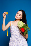 Beautiful sweet girl in a simple dress holding a cabbage and centimeter Royalty Free Stock Image
