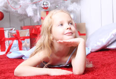 Beautiful sweet girl sits near a Christmas tree. She expects gifts and a Santa Claus when he comes. Girl lying on the red carpet Royalty Free Stock Image