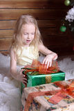Beautiful sweet girl sits near a Christmas tree. She opens the gift. She is very surprised and happy. Gift of green with orange bow Royalty Free Stock Photo