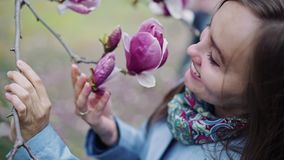 Beautiful sweet girl in surprise looks at a large beautiful flower of rich pink color in close-up. A beautiful sweet girl in surprise looks at a large beautiful stock footage