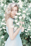 Beautiful sweet tender girl with blue eyes in a blue dress with light hair stranded in jasmine flowers stock image