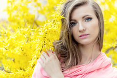 Beautiful sweetheart elegant girl in a pink jacket near shrub with yellow flowers stock photos