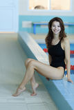 Beautiful swimmer woman at pool looking at camera. Portrait of competitive female swimmer near swimming pool. Royalty Free Stock Image