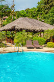 Beautiful swimming pool with rattandeck chairs Stock Photos