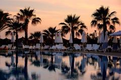 Beautiful swimming pool at sunset. Beautiful swimming pool and palm trees at sunset Stock Image