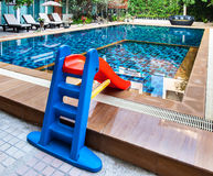 Beautiful swimming pool with tot slide. Royalty Free Stock Images