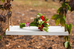 Beautiful swing, decorated ivy with bouquet Stock Photo