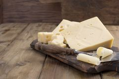 A beautiful Swiss cheese with holes, a useful dairy product. Tasty food. Country style photo. Place for text. Copy space stock image