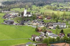 Beautiful Swiss village surrounded by green meadow and mountains. In summer Royalty Free Stock Photography