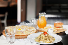 Beautiful table of italian pasta, pizza, burger and drinks. selective focus Stock Image