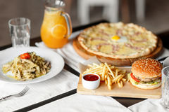 Beautiful table of italian pasta, pizza, burger and drinks. selective soft focus Stock Photography