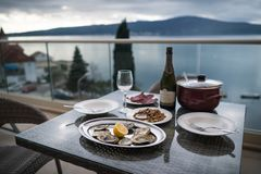 Beautiful table with local food and wine on the home balcony. Focus on oysters. Background of sea and mountains. Oysters with lemon, meat, snacks and bottle of royalty free stock photography