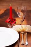 Beautiful table setting. With a candle in the background Royalty Free Stock Photos