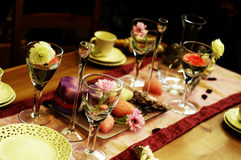 Beautiful table setting. Glasses and dishes beautifully arranged on a dining table, decorated with flowers stock images